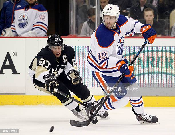 Justin Schultz of the Edmonton Oilers handles the puck in front of Sidney Crosby of the Pittsburgh Penguins during the game at Consol Energy Center...