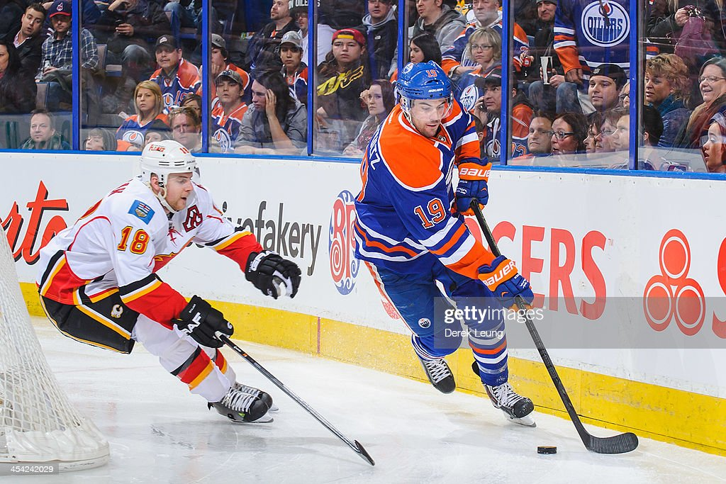 Justin Schultz #19 of the Edmonton Oilers skates with the puck past Matt Stajan #18 of the Calgary Flames during an NHL game at Rexall Place on December 7, 2013 in Edmonton, Alberta, Canada. The Flames defeated the Oilers 2-1 in overtime.