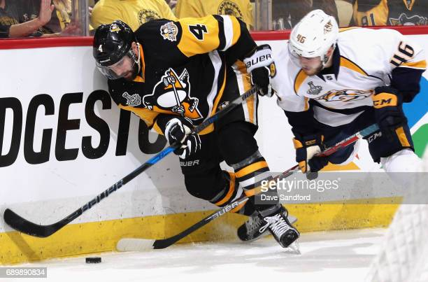Justin Schultz of the Pittsburgh Penguins and Pontus Aberg of the Nashville Predators battle for the puck at the boards during the third period of...