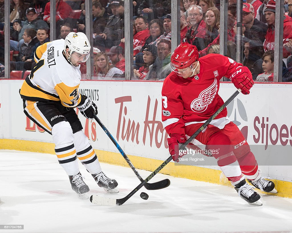 Justin Schultz #4 of the Pittsburgh Penguins battles for the puck with Nick Jensen #3 of the Detroit Red Wings during an NHL game at Joe Louis Arena on January 14, 2017 in Detroit, Michigan.