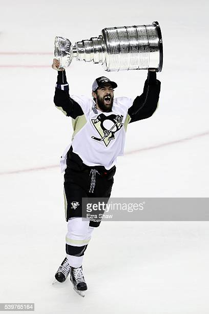Justin Schultz of the Pittsburgh Penguins celebrates by hoisting the Stanley Cup after a 31 victory over the San Jose Sharks in Game Six of the 2016...