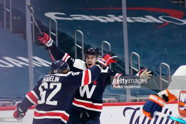 Justin Schultz of the Washington Capitals celebrates with teammate Carl Hagelin after scoring the game-winning goal against the New York Islanders in...