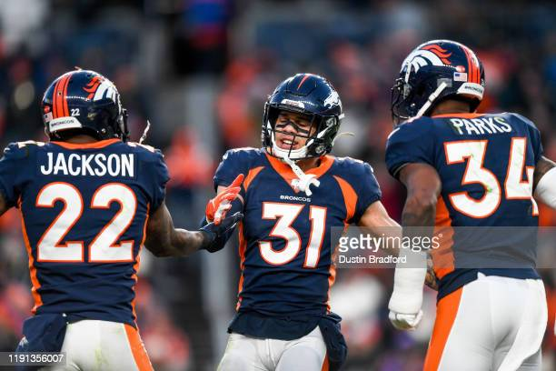 Justin Simmons of the Denver Broncos celebrates a defensive stop with Kareem Jackson and Will Parks in the third quarter of a game at Empower Field...