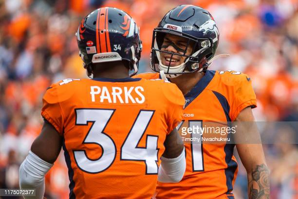 Justin Simmons of the Denver Broncos celebrates a tackle with teammate Will Parks at Empower Field at Mile High on September 15 2019 in Denver...
