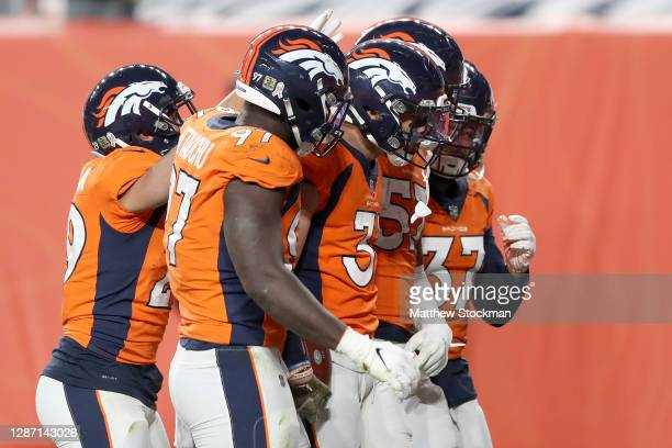 Justin Simmons of the Denver Broncos celebrates his interception with Bryce Callahan Jeremiah Attaochu DeMarcus Walker and PJ Locke during the fourth...