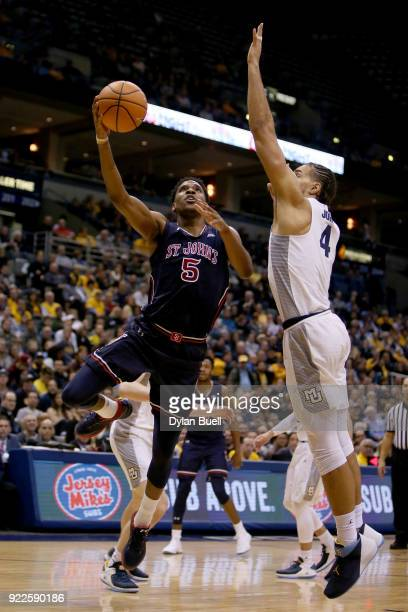 Justin Simon of the St John's Red Storm attempts a shot while being guarded by Theo John of the Marquette Golden Eagles in the second half at the BMO...
