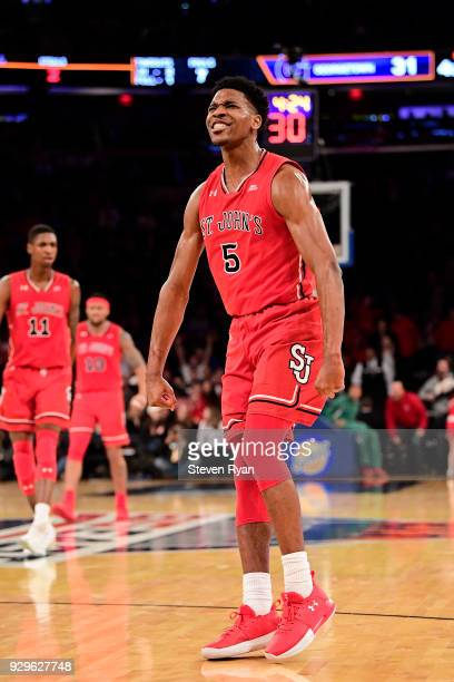 Justin Simon of the St John's Red Storm celebrates after dunking the ball against the Georgetown Hoyas during the first round of the Big East...