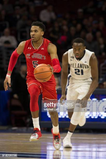 Justin Simon of the St John's Red Storm dribbles the ball against Dhamir CosbyRoundtree of the Villanova Wildcats at the Wells Fargo Center on...