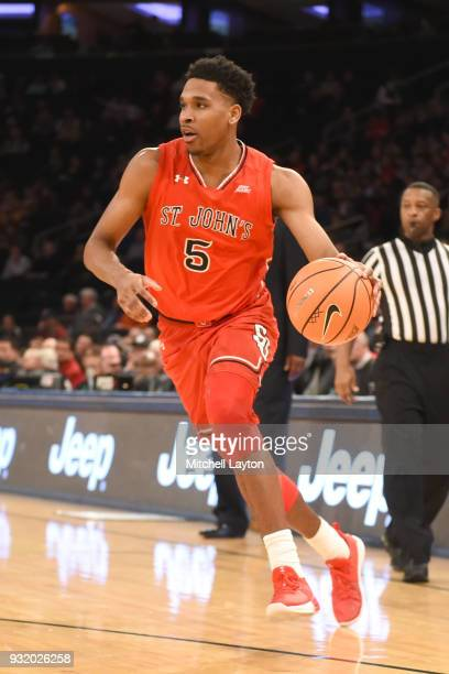 Justin Simon of the St John's Red Storm dribbles the ball during the 1st round of the Big East Basketball Tournament against the Georgetown Hoyas at...