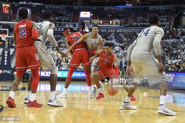 Justin Simon of the St John's Red Storm dribbles through traffic during a college basketball game against the Georgetown Hoyas at the Capital One...