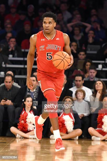 Justin Simon of the St John's Red Storm dribbles up court during the 1st round of the Big East Basketball Tournament against the Georgetown Hoyas at...