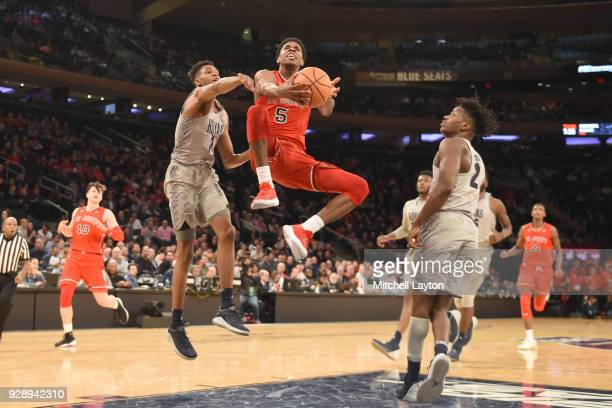 Justin Simon of the St John's Red Storm drives to the basket basket Jamorko Pickett of the Georgetown Hoyas during the first round of the Big East...