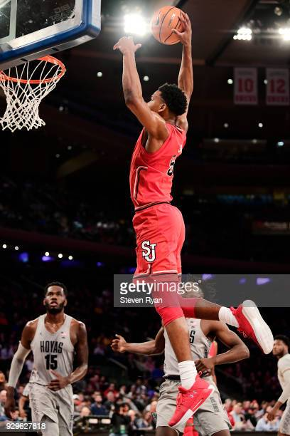 Justin Simon of the St John's Red Storm dunks the ball against the Georgetown Hoyas during the first round of the Big East tournament at Madison...