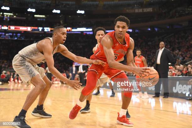 Justin Simon of the St John's Red Storm tires to get around Kaleb Johnson of the Georgetown Hoyas during the 1st round of the Big East Basketball...