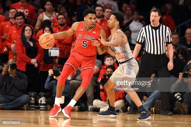 Justin Simon of the St John's Red Storm tries to dribbles around Jahvon Blair of the Georgetown Hoyas during the 1st round of the Big East Basketball...