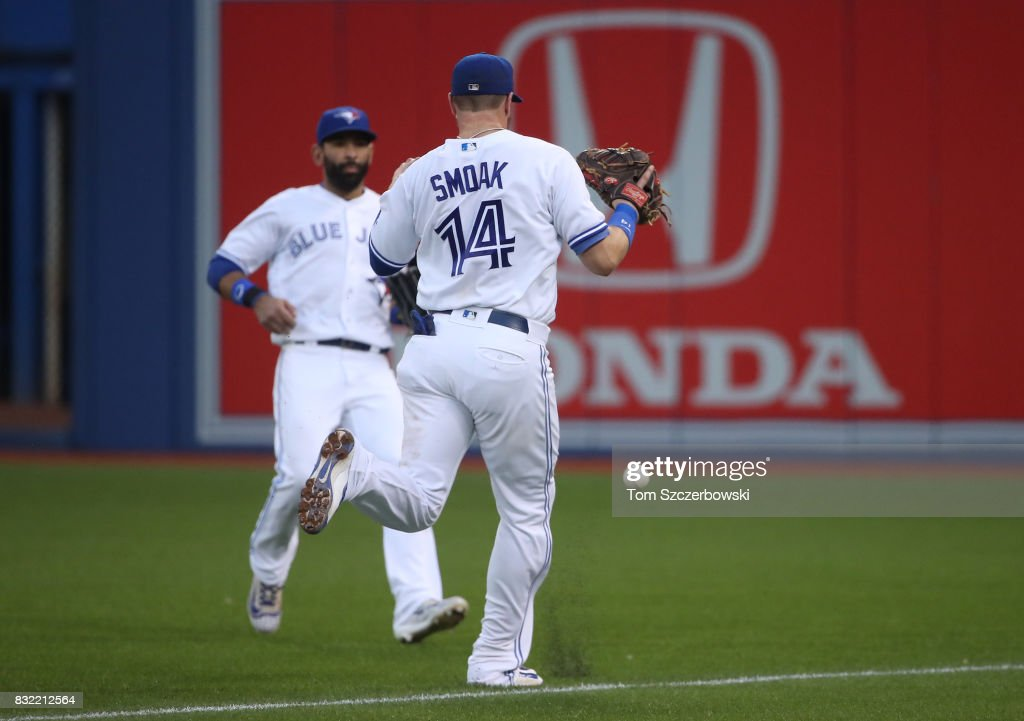 Justin Smoak #14 and Jose Bautista #19 of the Toronto Blue Jays converge but the ball drops in fair territory for a double off the bat of Adeiny Hechavarria of the Tampa Bay Rays in the fourth inning during MLB game action at Rogers Centre on August 15, 2017 in Toronto, Canada.