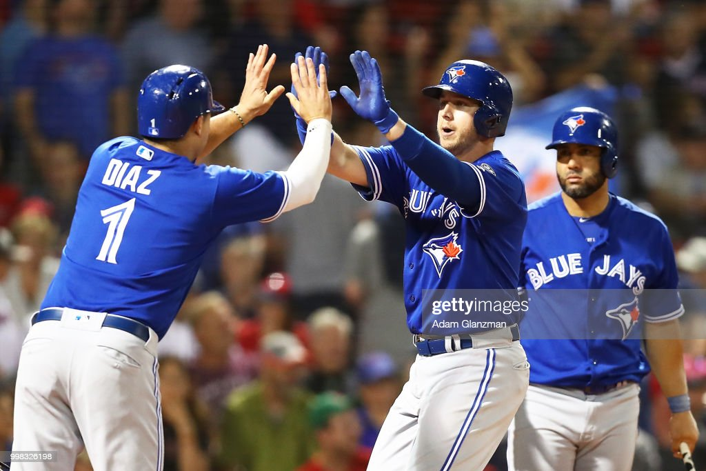 Justin Smoak #14 high fives Aledmys Diaz #1 of the Toronto Blue Jays after hitting a two-run home run in the ninth inning of a game against the Boston Red Sox at Fenway Park on July 13, 2018 in Boston, Massachusetts.