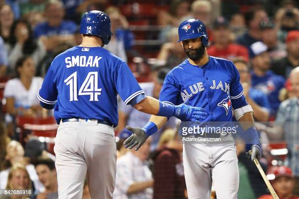 Justin Smoak high fives Jose Bautista of the Toronto Blue Jays after hitting a solo home run in the ninth inning of a game against the Boston Red Sox...