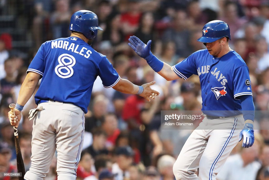Justin Smoak #14 high fives Kendrys Morales #8 of the Toronto Blue Jays after scoring in the third inning of a game against the Boston Red Sox at Fenway Park on July 13, 2018 in Boston, Massachusetts.