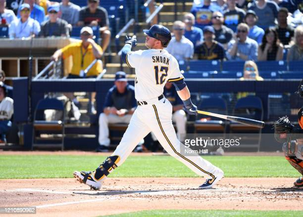 Justin Smoak of the Milwaukee Brewers follows through on a swing during a spring training game against the San Francisco Giants at American Family...