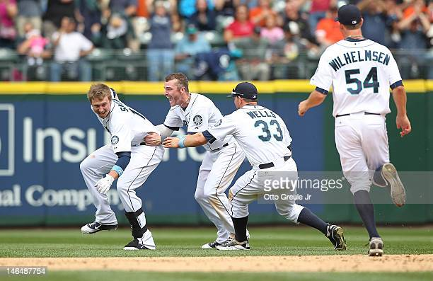 Justin Smoak of the Seattle Mariners is mobbed by teammates after he hit a game winning single to defeat the San Francisco Giants 21 at Safeco Field...