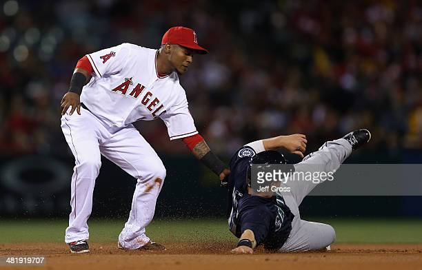 Justin Smoak of the Seattle Mariners is tagged out by shortstop Erick Aybar of the Los Angeles Angels of Anaheim during a steal attempt in the second...