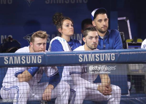 Justin Smoak of the Toronto Blue Jays and head athletic trainer Nikki Huffman and Randal Grichuk and Marco Estrada look on from the top step of the...
