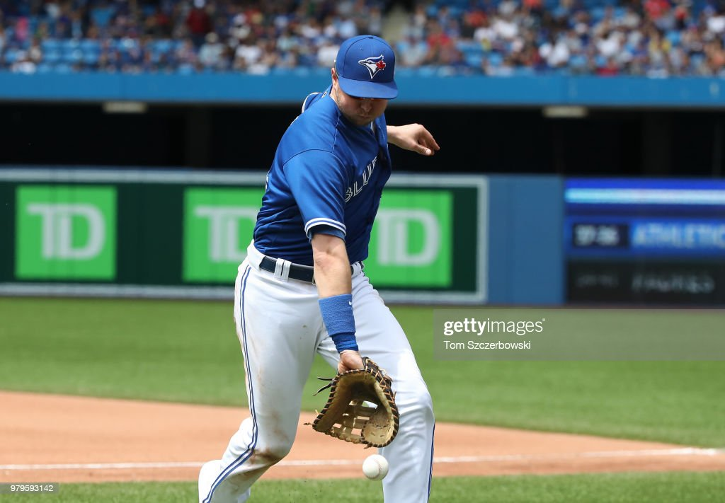 Justin Smoak #14 of the Toronto Blue Jays can't make the play on a foul pop up in the seventh inning during MLB game action against the Atlanta Braves at Rogers Centre on June 20, 2018 in Toronto, Canada.