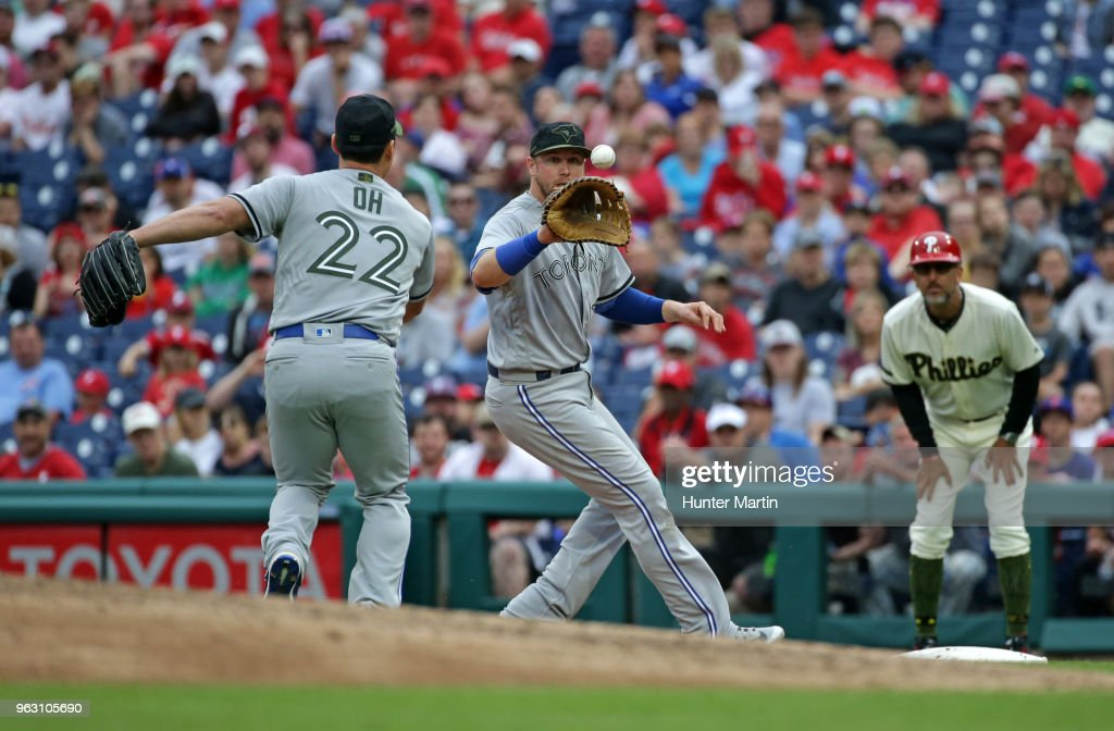 Justin Smoak #14 of the Toronto Blue Jays catches a throw from Seung Hwan Oh #22 for a ground out in the seventh inning during a game against the Philadelphia Phillies at Citizens Bank Park on May 27, 2018 in Philadelphia, Pennsylvania. The Blue Jays won 5-3.