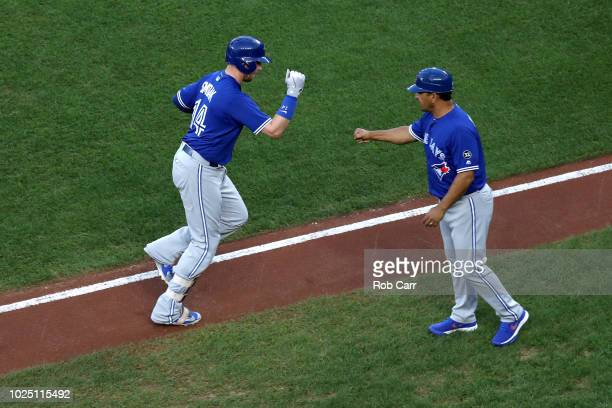 Justin Smoak of the Toronto Blue Jays celebrates his first inning solo home run with third base coach Luis Rivera against the Baltimore Orioles at...