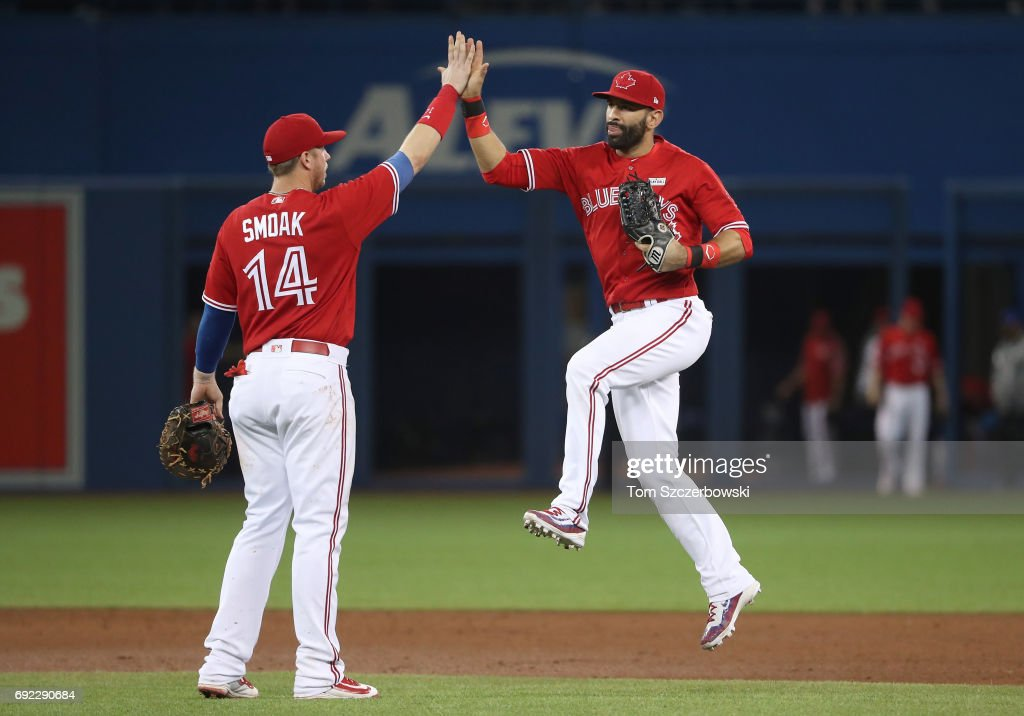 Justin Smoak #14 of the Toronto Blue Jays celebrates their victory with Jose Bautista #19 during MLB game action against the New York Yankees at Rogers Centre on June 4, 2017 in Toronto, Canada.
