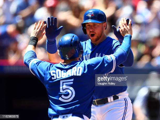 Justin Smoak of the Toronto Blue Jays celebrates with Eric Sogard after hitting a 2 run home run in the second inning during a MLB game against the...