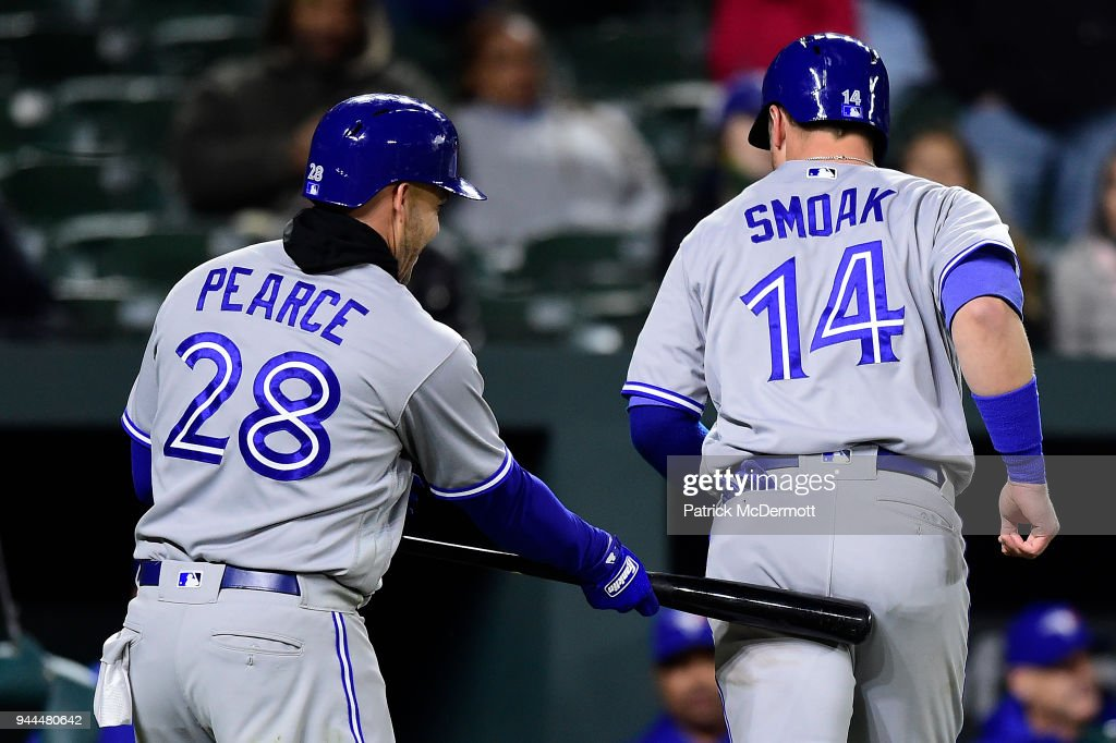 Justin Smoak #14 of the Toronto Blue Jays celebrates with Steve Pearce #28 after scoring on a single hit by Yangervis Solarte #26 (not pictured) in the eighth inning against the Baltimore Orioles at Oriole Park at Camden Yards on April 10, 2018 in Baltimore, Maryland.