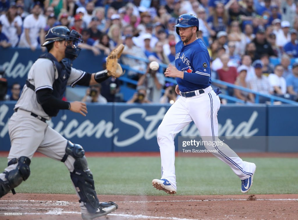 Justin Smoak #14 of the Toronto Blue Jays comes in to score a run on a sacrifice fly by Kevin Pillar #11 in the sixth inning during MLB game action as Kyle Higashioka #66 of the New York Yankees takes the late throw at Rogers Centre on July 7, 2018 in Toronto, Canada.