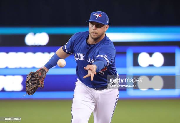 Justin Smoak of the Toronto Blue Jays flips the ball to the pitcher covering first base after fielding a grounder to get the baserunner at first base...