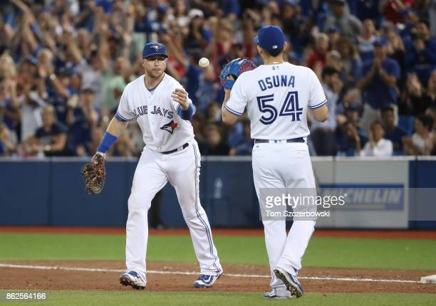 Justin Smoak of the Toronto Blue Jays flips the baseball to Roberto Osuna as Osuna records his 30th save of the season after getting the final out of...
