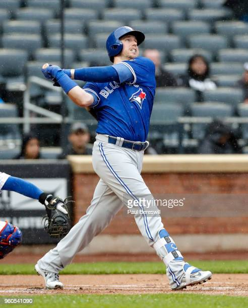 Justin Smoak of the Toronto Blue Jays hits a home run in an interleague MLB baseball game against the New York Mets during a steady rain on May 16...