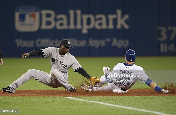Justin Smoak of the Toronto Blue Jays is caught trying to stretch an RBI single into a double but is tagged out at second base by Didi Gregorius of...
