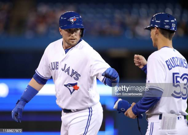 Justin Smoak of the Toronto Blue Jays is congratulated by first base coach Mark Budzinski after hitting a single in the fourth inning during MLB game...