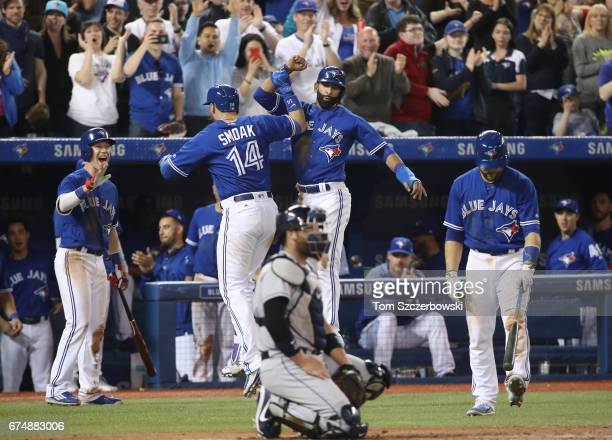 Justin Smoak of the Toronto Blue Jays is congratulated by Jose Bautista after hitting a tworun home run in the sixth inning during MLB game action...
