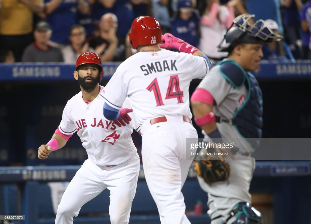 Justin Smoak #14 of the Toronto Blue Jays is congratulated by Jose Bautista #19 after hitting a two-run home run in the sixth inning during MLB game action against the Seattle Mariners at Rogers Centre on May 14, 2017 in Toronto, Canada.