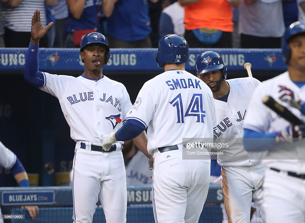 Justin Smoak #14 of the Toronto Blue Jays is congratulated by Melvin Upton Jr. #7 and Jose Bautista #19 after hitting a three-run home run in the second inning during MLB game action against the Minnesota Twins on August 26, 2016 at Rogers Centre in Toronto, Ontario, Canada.