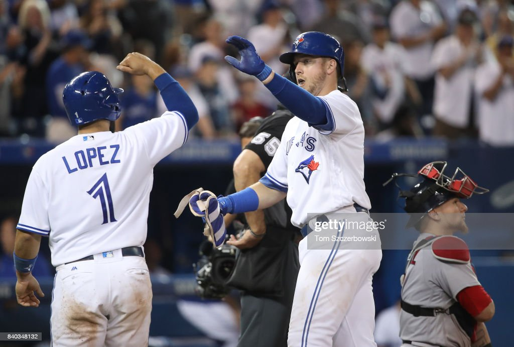 Justin Smoak #14 of the Toronto Blue Jays is congratulated by Raffy Lopez #1 after hitting a two-run home run in the ninth inning during MLB game action against the Boston Red Sox at Rogers Centre on August 28, 2017 in Toronto, Canada.
