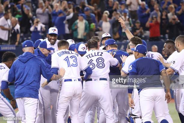 Justin Smoak of the Toronto Blue Jays is congratulated by teammates at home plate after hitting a gamewinning solo home run in the ninth inning...