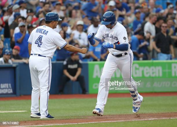 Justin Smoak of the Toronto Blue Jays is congratulated by third base coach Luis Rivera after hitting a tworun home run in the fourth inning during...