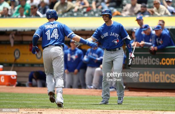 Justin Smoak of the Toronto Blue Jays is congratulated by Troy Tulowitzki after he hit a home run against the Oakland Athletics in the second inning...