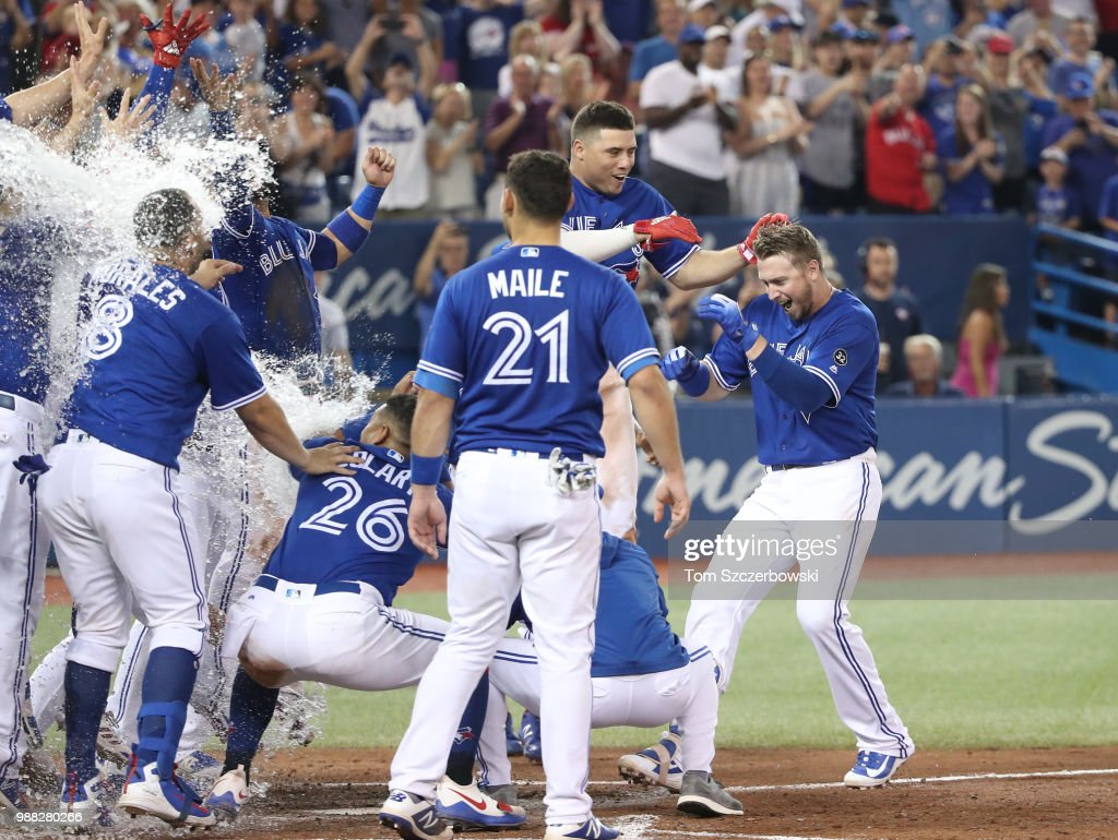 Justin Smoak #14 of the Toronto Blue Jays is greeted at home plate by teammates who congratulate him after hitting a game-winning solo home run in the ninth inning during MLB game action against the Detroit Tigers at Rogers Centre on June 30, 2018 in Toronto, Canada.