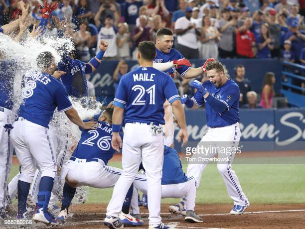 Justin Smoak of the Toronto Blue Jays is greeted at home plate by teammates who congratulate him after hitting a gamewinning solo home run in the...