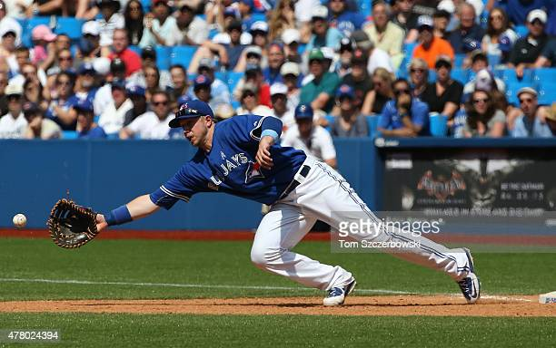 Justin Smoak of the Toronto Blue Jays is pulled off first base by an errant throw from Steve Delabar in the eighth inning during MLB game action as...