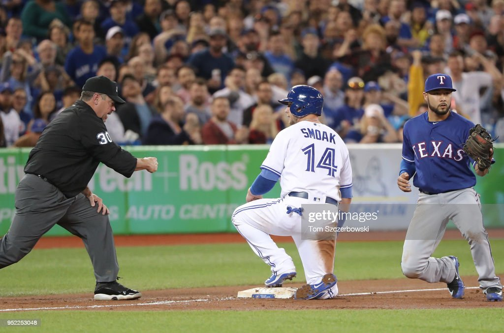 Justin Smoak #14 of the Toronto Blue Jays is throw out trying advance to third base as third base umpire Rob Drake #30 makes the out call in the third inning during MLB game action against the Texas Rangers at Rogers Centre on April 27, 2018 in Toronto, Canada.